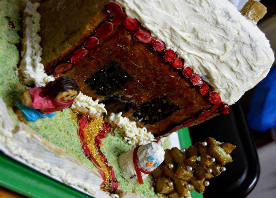 A crooked picture of a homemade gingerbread house. The roof is of a white iceing badly spread, the walls are uneavenly covered in caramel, there is a gingerbread man with a face so badly drawn is almost scary and a white truffe snowman that looks quite sad.