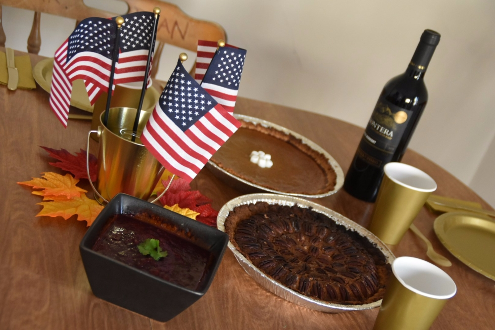A wooden table featuring a black bowl with cranberry sauce, a pecan pie, a pumkin pie with marshmallows, and a bottle of red wine. The table is set up with golden cardboard and plastic dinnerware, and decorated with American flags and fake maple leaves in orange, yellow and red tones.