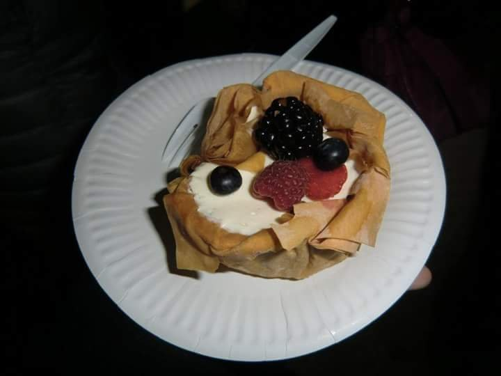 A white paper plate with a parcel cheesecake in the middle. It looks like a bowl-shaped crepe with a white creamy filling and berries on top.