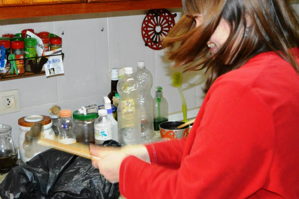 Iris is beating a black plastic bag with a hammer. Her face is covered by her hair because of the motion, but her big smile can still be glimpsed. The kitchen is rather messy, with tons of containers and bottles everywhere.