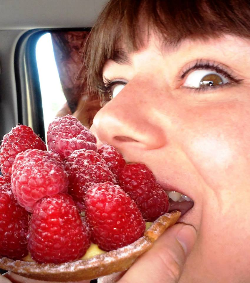 A close-up of Iris eating a raspberry tart, with a mountain of raspberries, not only a few.