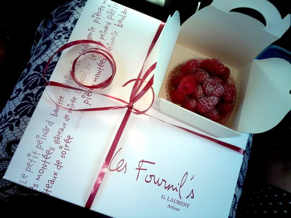 A white pastry box with a read bow and the logo of the bakery Les Fournil's, Artisan G. Laurent.
