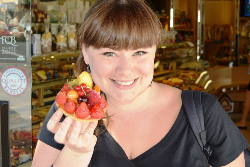 Iris, with a big smile, holding a small tart with strawberries, kiwi, peach, apple, a cherry, a raspberry and some bilberries on it.