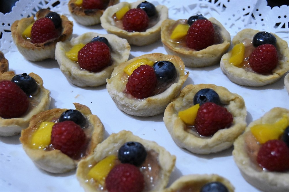 A white plate with three rows of small homemade tarts, each topped with a rasberry, a bluebery and a small piece of mango.