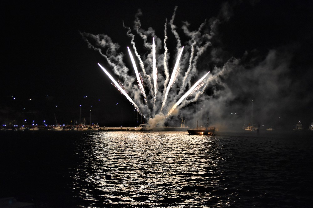 White fireworks emerging from a dark sea illuminate a small burnt boat with glowing embers.