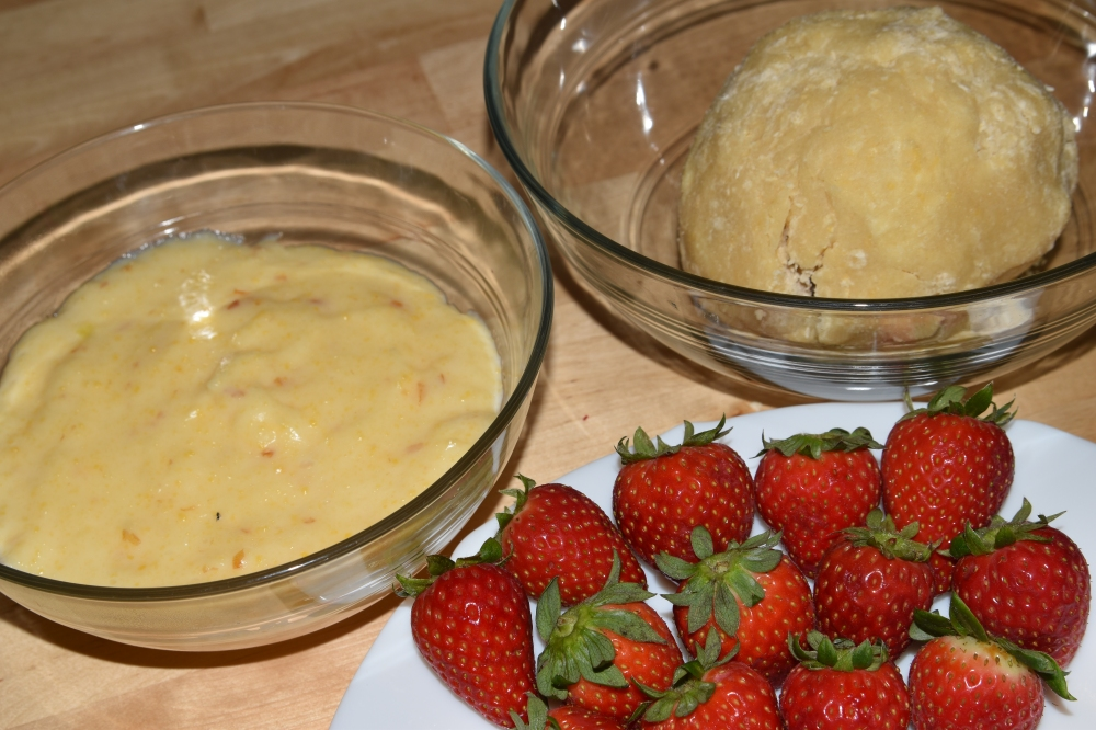 In two separate glass bowls, there is some custard and a ball of pie dough. Next to them, to the right, there is a white plate with strawberries.