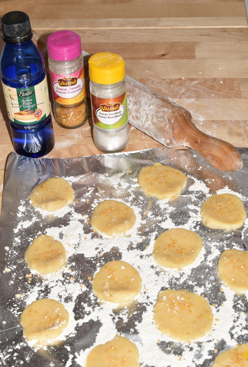 Unbaked cookies laying on a aluminium sheet with flour. Next to it, a plastic bottle of orange blossom water, a golden sugar jar, and a vanilla sugar jar stand next to the rolling pin.