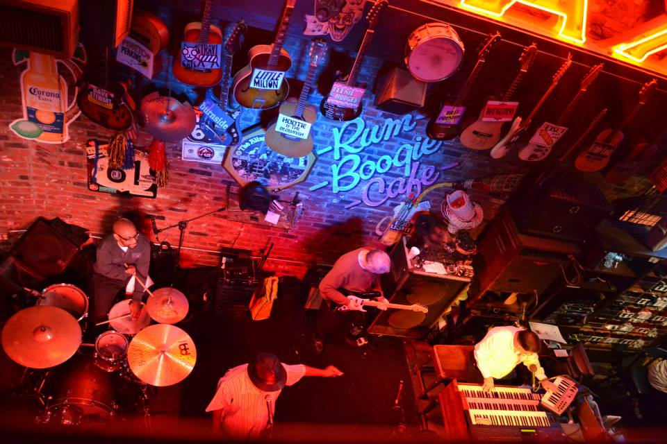 Aerial view of the Rum Boogie Café stage, with four man playing on it: a drummer, a guitarist, a singer with a hat, and a pianist. On the brick wall, the name of the bar is lightened in blue, while the rest of the place is under a red light. Also, about a dozen guitars are hanging from the wall.