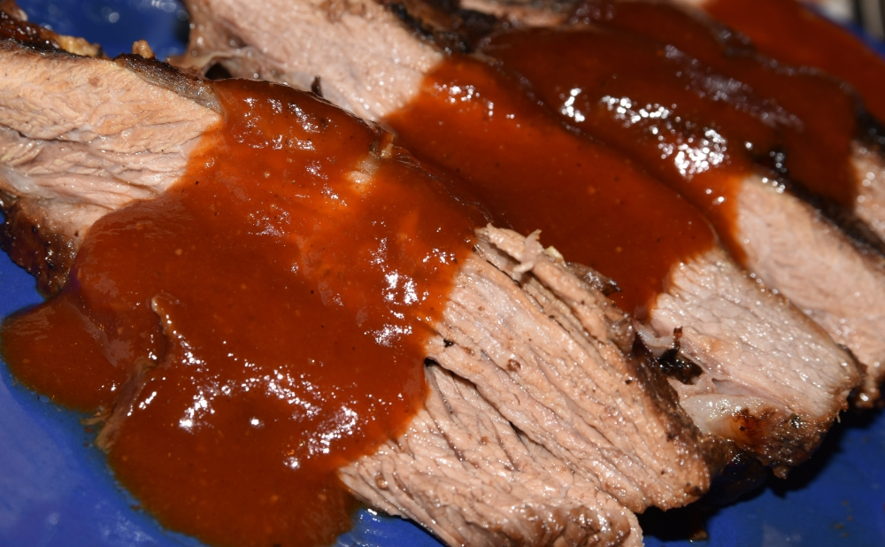 A close-up of five cuts of pork brisket, laid in a line, with a trail of instense red barbecue sauce in the middle.